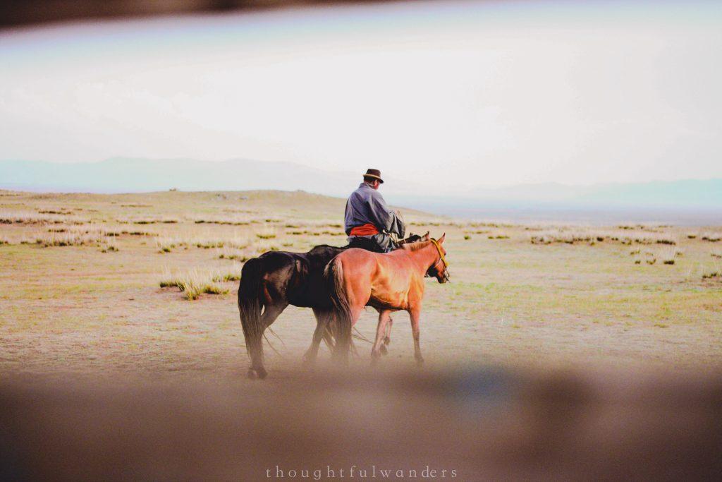 Mongolian man riding horse slowly