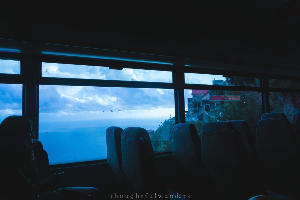 Amalfi Coast bus view seeing past passenger silhouette with ocean in the background