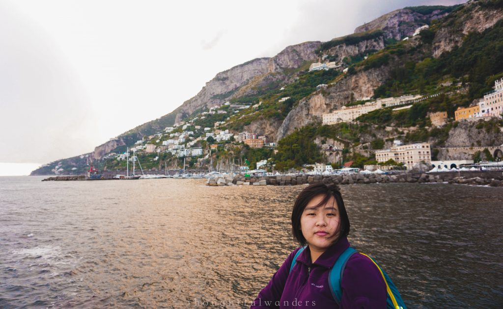 Asian woman looking at the camera with Amalfi in the background Amalfi Coast, Italy