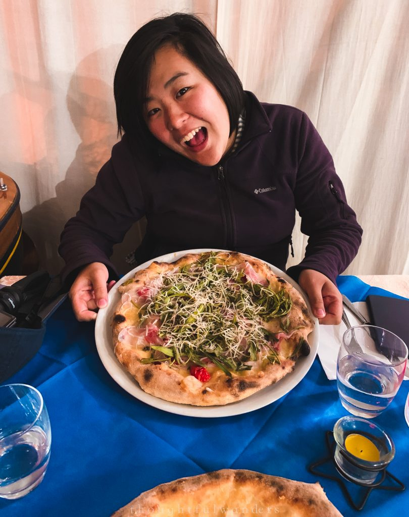 Asian woman excited to eat Italian pizza