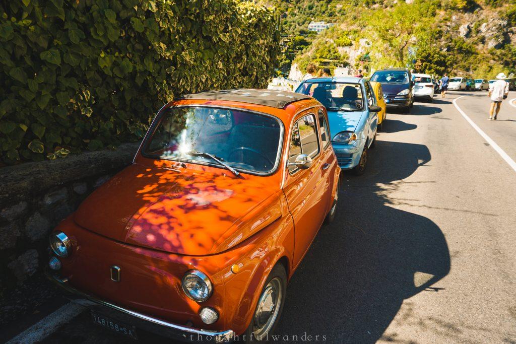 Red Italian car parked on the side of the road near Positano Amalfi Coast