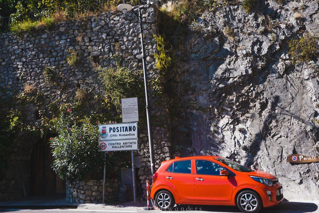 Red car parked next to sign that says Positano