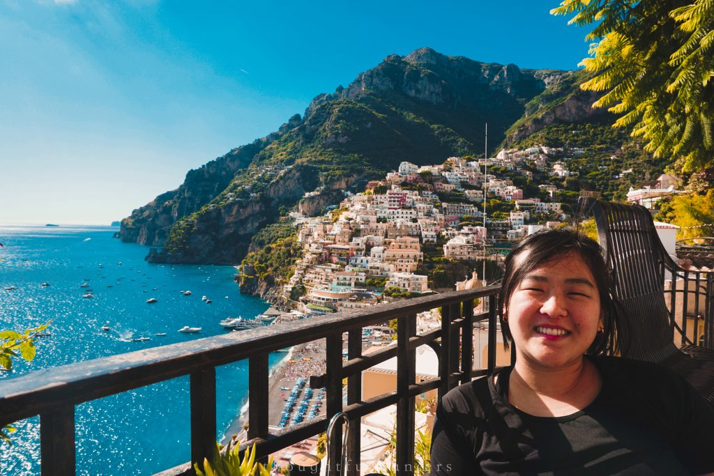 Asian woman smiling at camera next to Positano