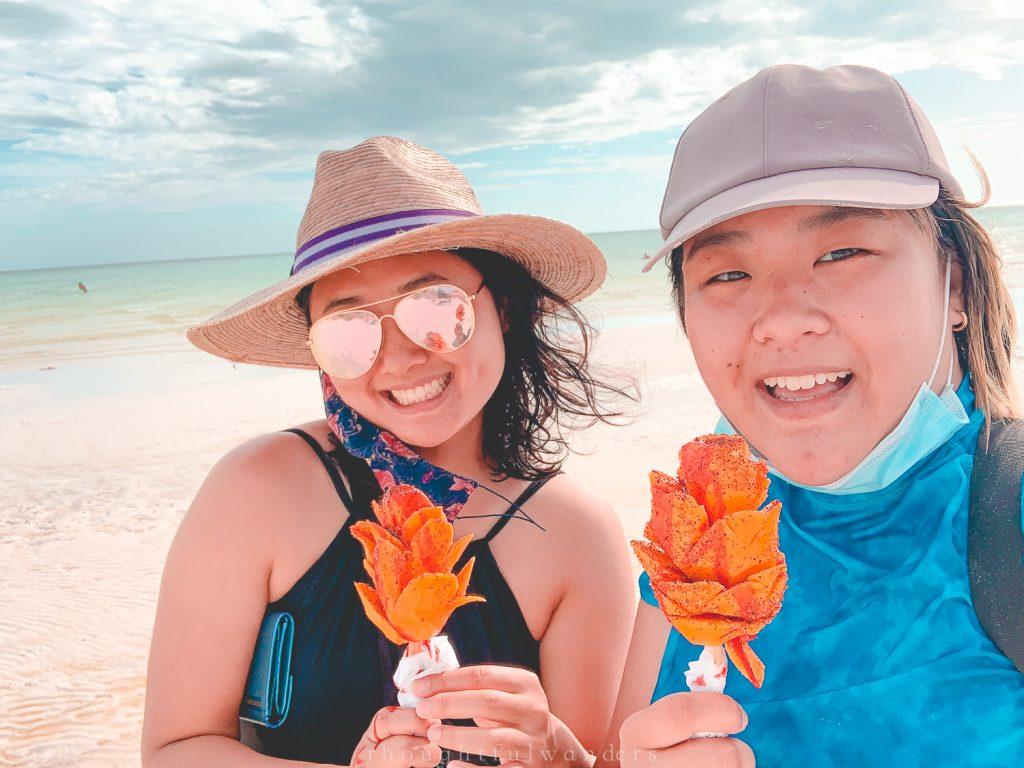 Two Asian women eating mango tajin