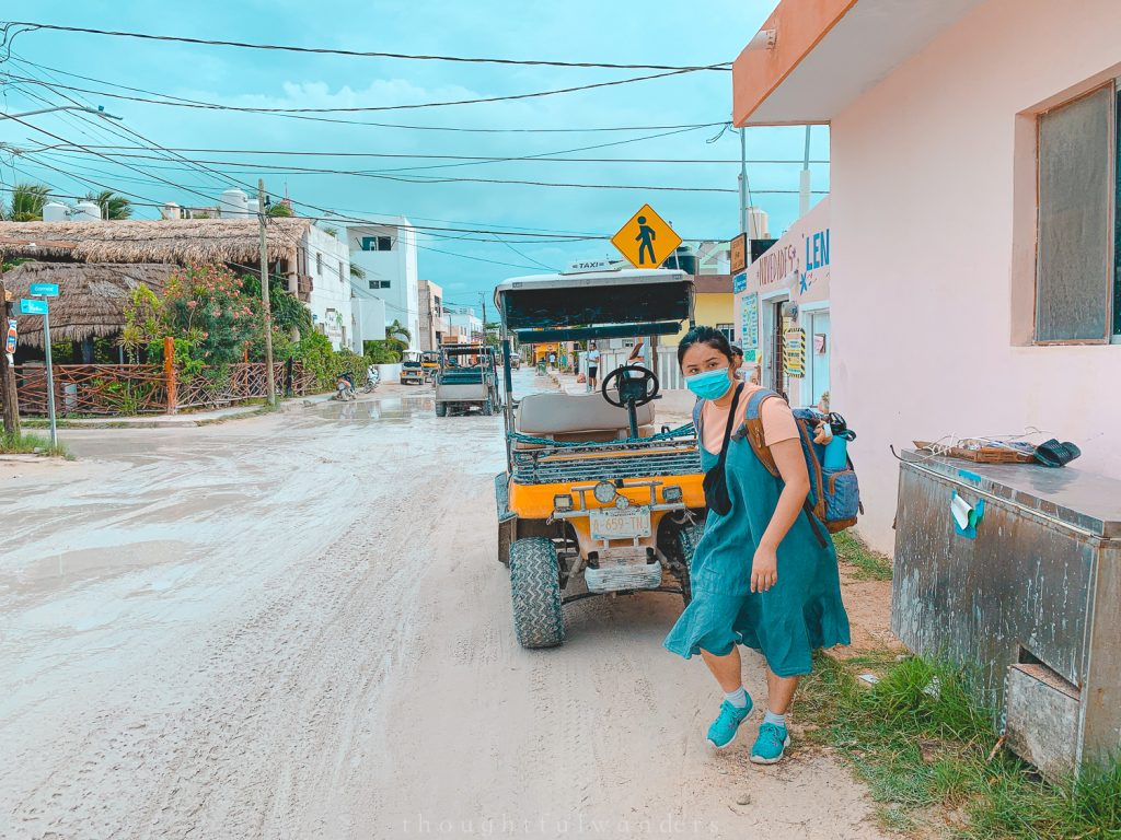 Asian woman with mask walking with luggage on Isla Holbox