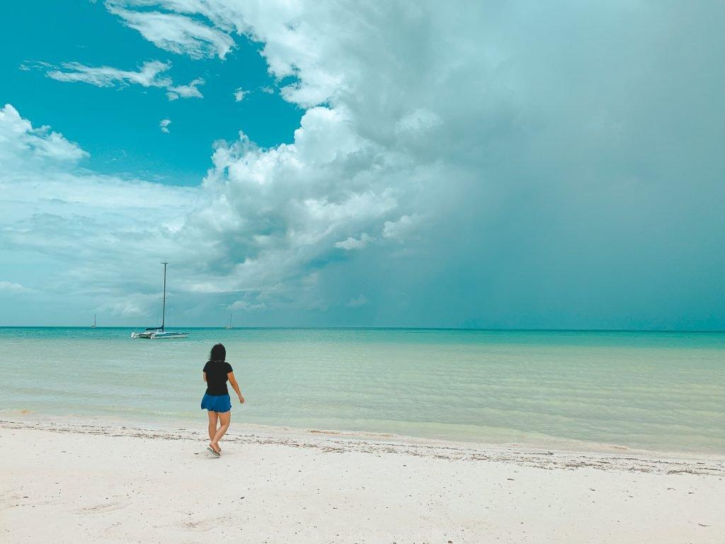 Asian woman walking on the beach Isla Holbox