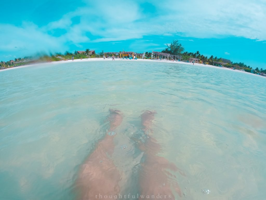 View of Asian woman legs sitting inside water at Isla Holboxolbox