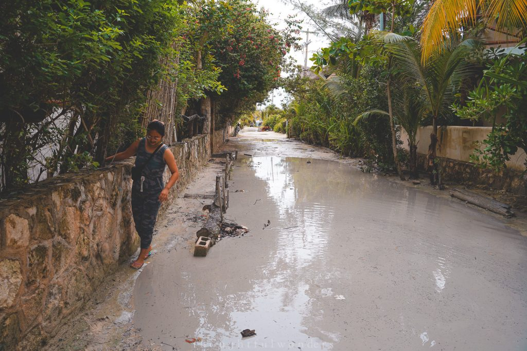Asian woman dodging puddles in Isla Holboxolbox