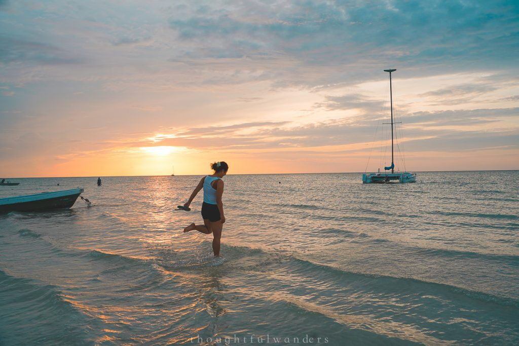 Asian woman skipping into the ocean at Isla Holbox