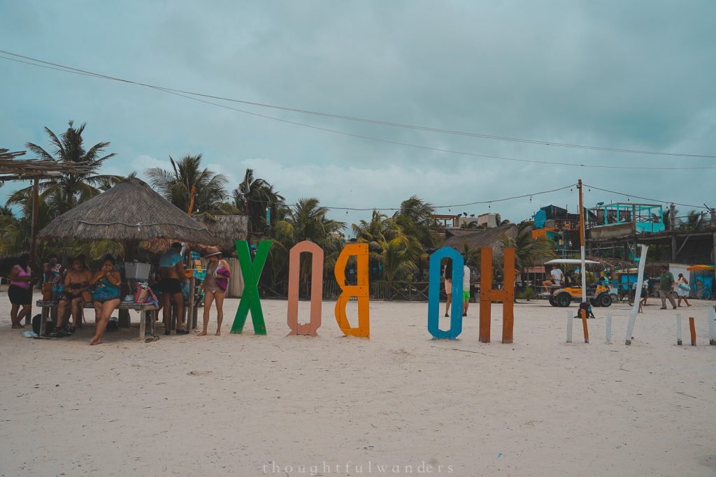 Tourists at Holbox hanging out under a beach sign