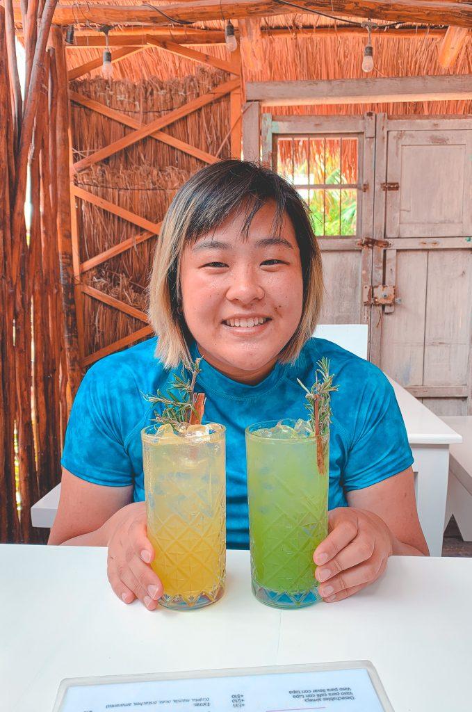 Asian woman posing with two aguas frescas