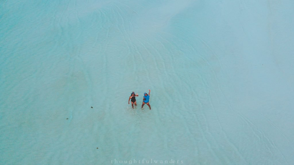 Two Asian women drone footage by the beach at Isla Holbox