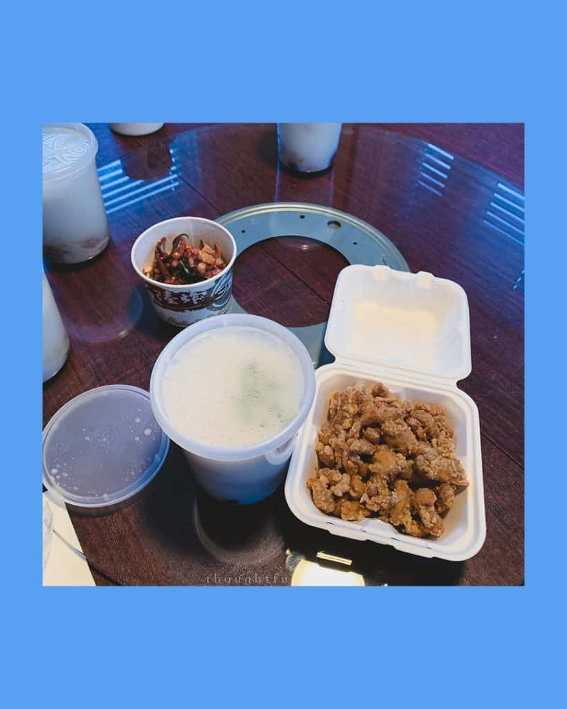 Take out containers with congee, squid, and Taiwanese popcorn chicken on a round table