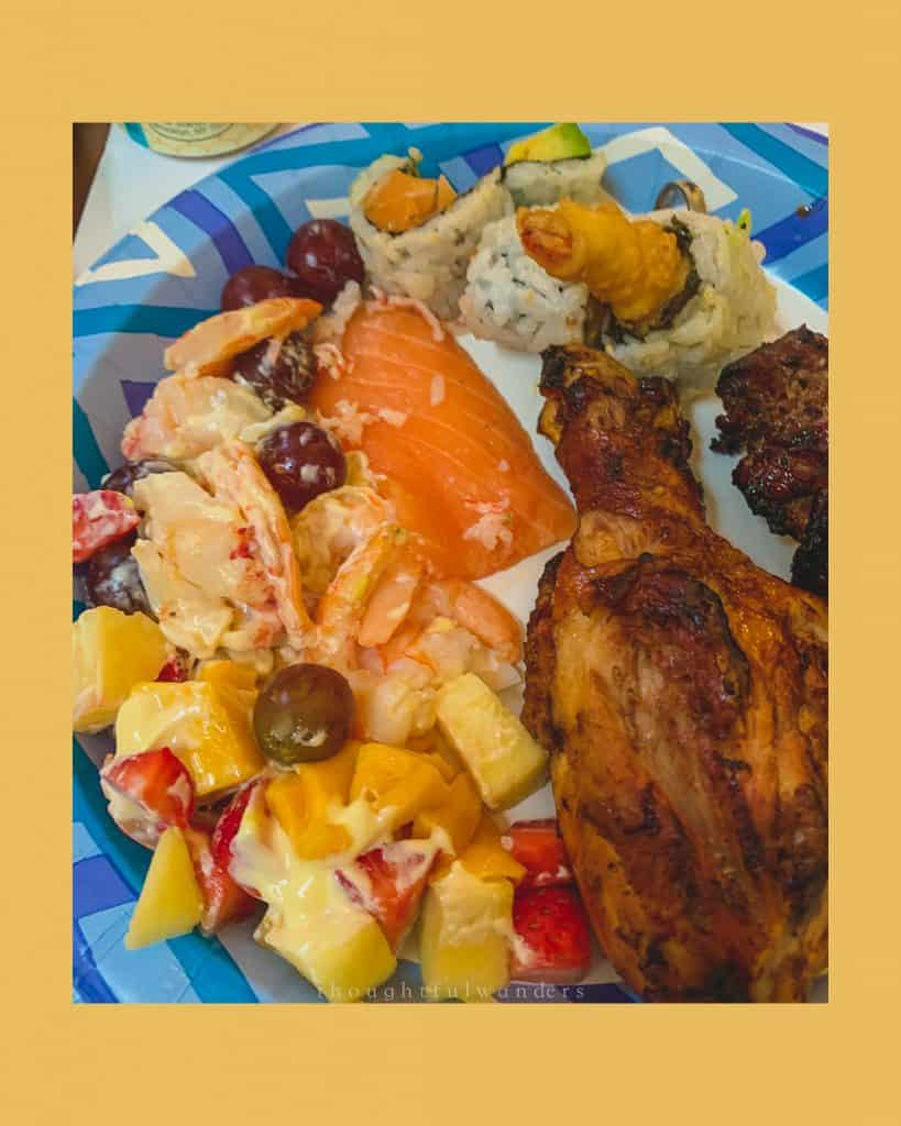 Plate with food including chicken drumsticks, sashimi, shrimp fruit salad, and sushi. Photo has yellow borders