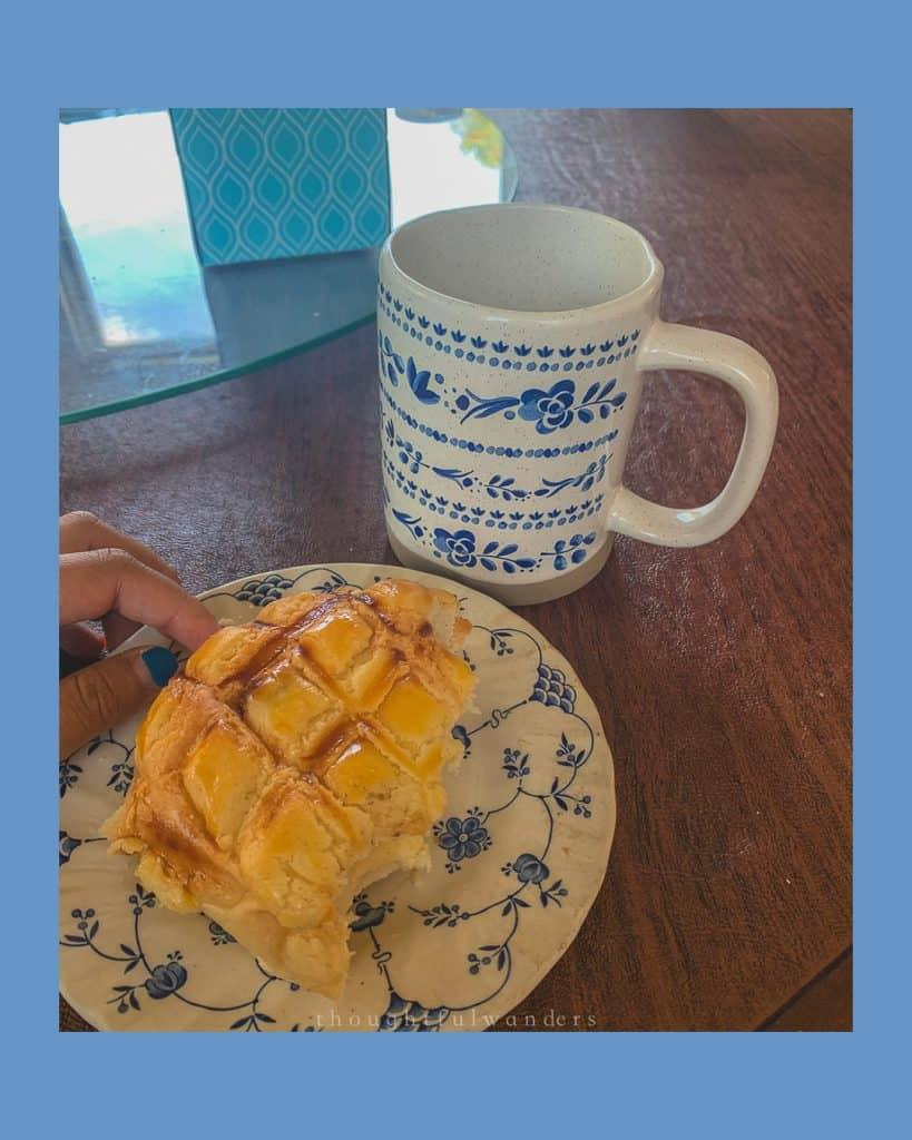 Taiwanese Pineapple bun (bolo bao) next to nice ceramic mug. photo has blue borders
