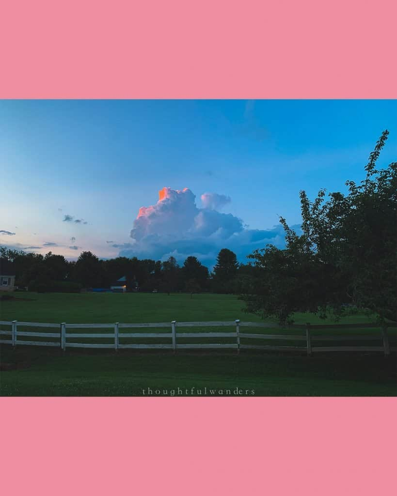 Sunset with fluffy clouds that have pink/orange glow in the cloud in suburban Maryland