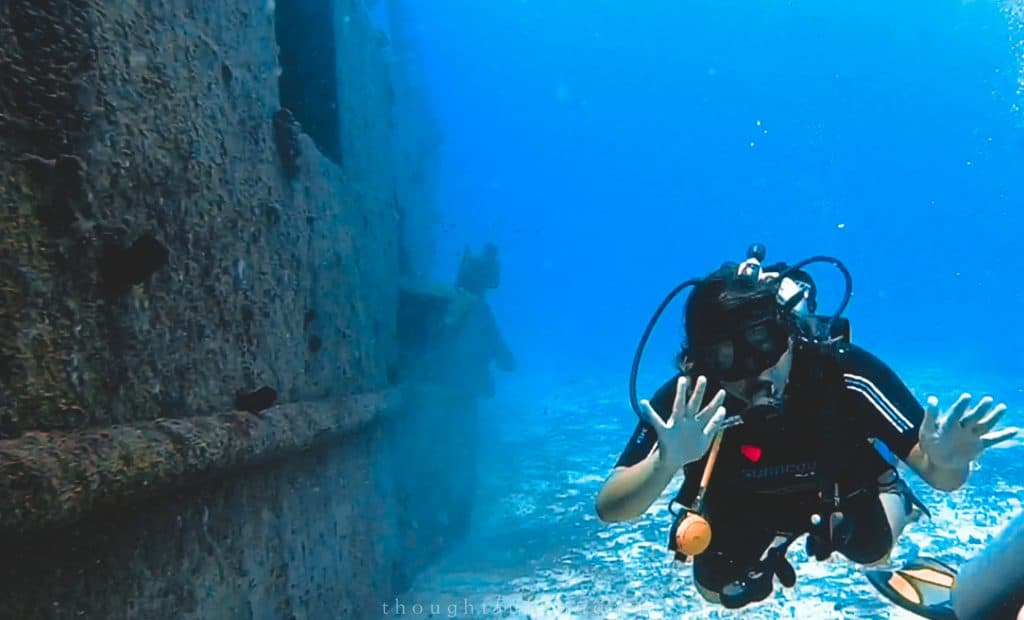 Asian woman waving to the camera while swimming next to the wreck