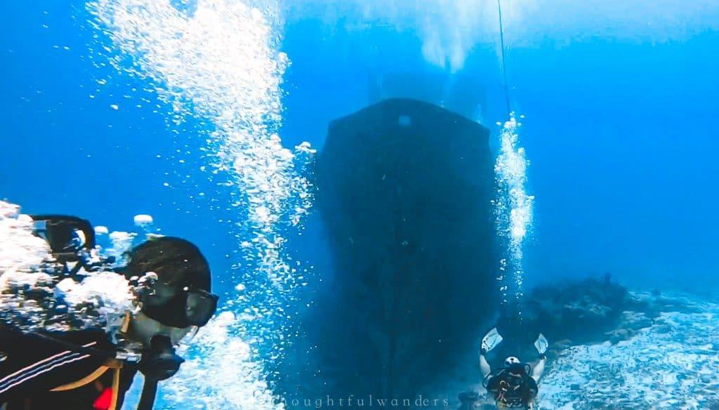 Asian woman scuba diving next to ship wreck looking at the camera