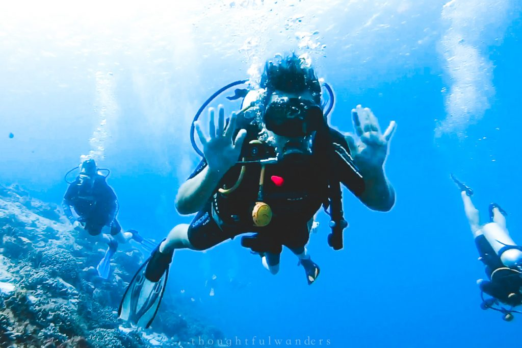 Asian woman scuba diving waving to camera